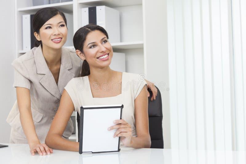 Asiatische chinesische u. hispanische Geschäftsfrauen, die Tablet-Computer verwenden lizenzfreie stockbilder