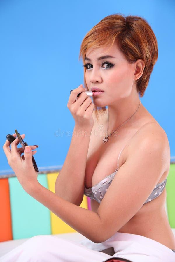 Asiatische Dame, die Lippenstift im sexy Kleid anwendet. stockfotografie