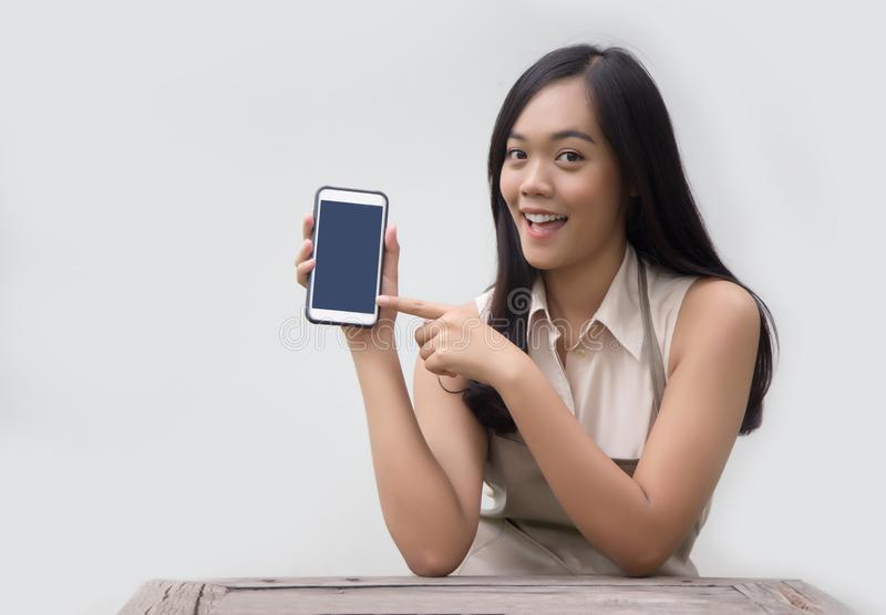Asiatische Dame mit Kittelschürzeblickpunkt am mobilen Schirm lizenzfreies stockfoto