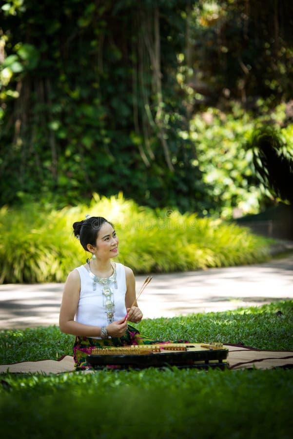 Asiatische Dame mit Lächeln in thailändischem traditionellem möchten ankleiden sitzen und pl stockfotos