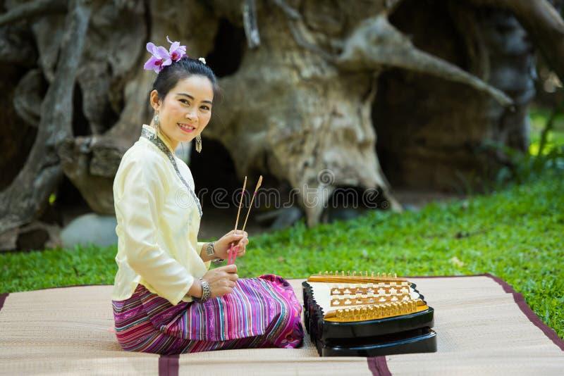 Asiatische Dame mit Lächeln in thailändischem traditionellem möchten ankleiden sitzen und pl lizenzfreie stockfotografie