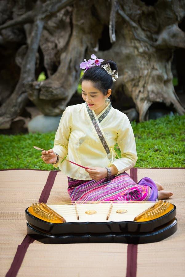 Asiatische Dame mit Lächeln in thailändischem traditionellem möchten ankleiden sitzen und pl lizenzfreie stockbilder