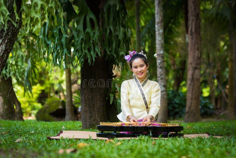 Asiatische Dame mit Lächeln in thailändischem traditionellem möchten ankleiden sitzen und pl lizenzfreies stockfoto