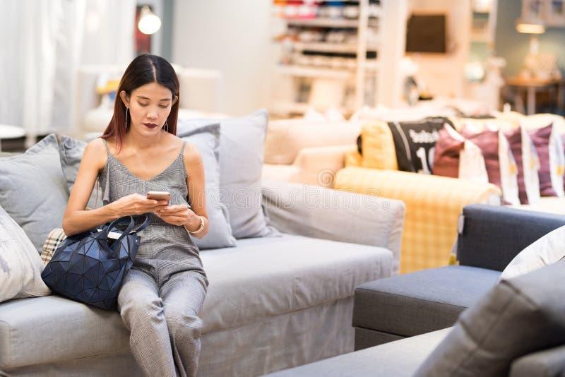 Asiatische Dame sitzen auf Sofa und benutzen intelligenten Handy, um in Verbindung zu stehen lizenzfreie stockfotografie