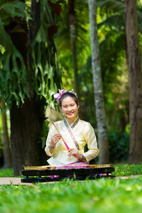 Asiatische Dame in thailändischem traditionellem möchten ankleiden sitzen und das d spielend lizenzfreies stockfoto