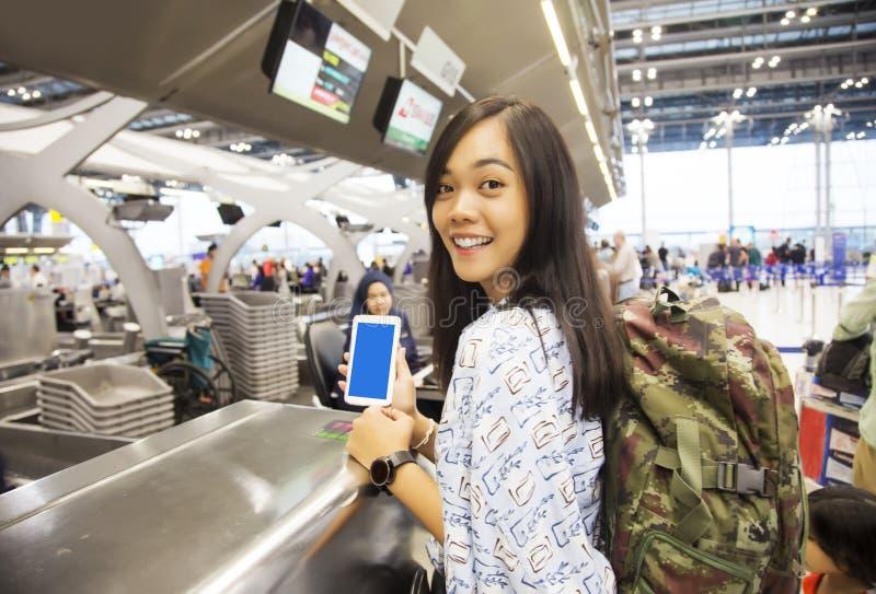 Asiatische Damenkontrolle im Flug mit ihrem Mobile lizenzfreies stockbild