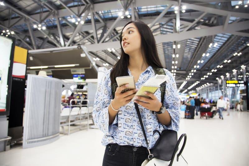 Asiatische Damenkontrolle im Flug mit ihrem Mobile lizenzfreies stockfoto