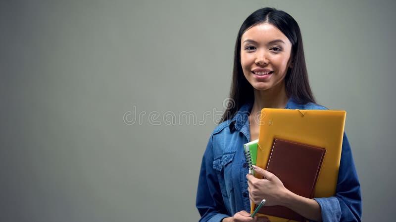 Asiatische Damenstellung mit Schreibheften, Studentenaustauschprogramm, grauer Hintergrund lizenzfreies stockfoto