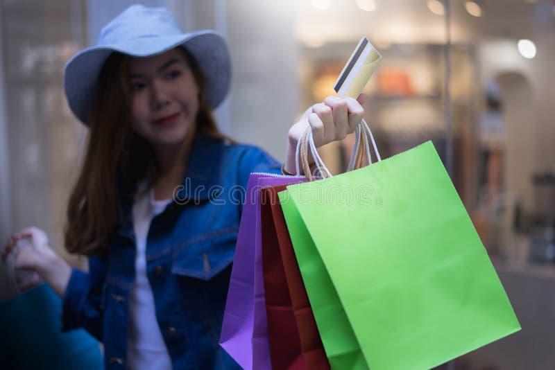 Asiatische Einkaufsfrau, die Kredit oder Debitkarte und Einkaufstaschen am Einkaufszentrum h?lt Verbraucherschutzbewegung, Lebens stockfotos