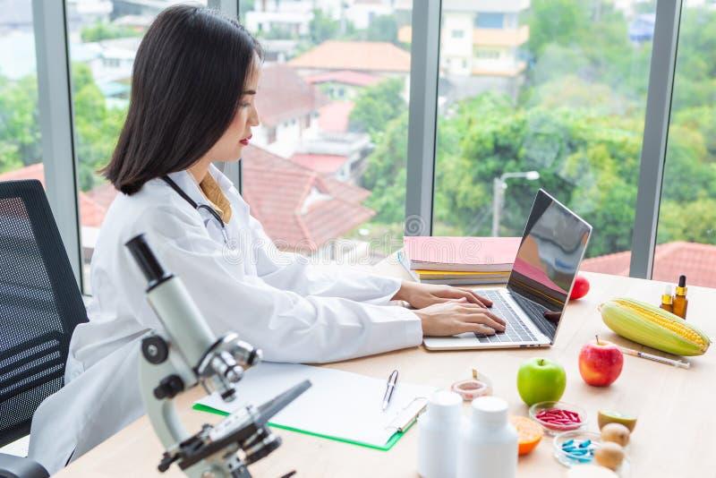 Asiatische Ernährungswissenschaftlerdoktor-Frau Arbeits-labtop mit Mikroskop auf Holztisch lizenzfreie stockfotos