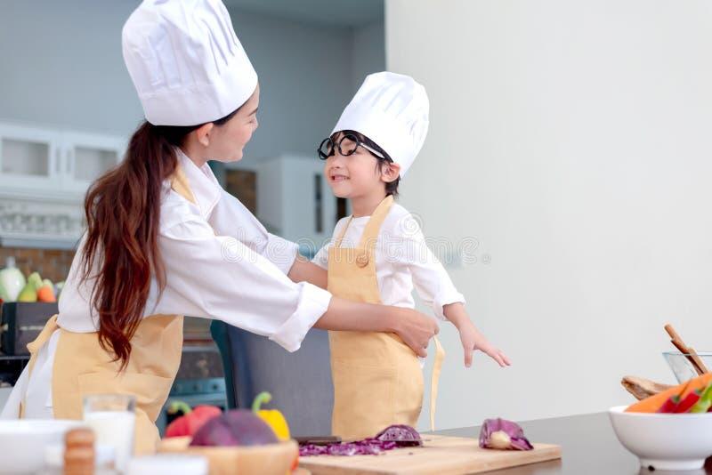 Asiatische Familie in der K?che Unterrichtender Sohn der Mutter für gesunde Nahrung des Kochs lizenzfreies stockbild