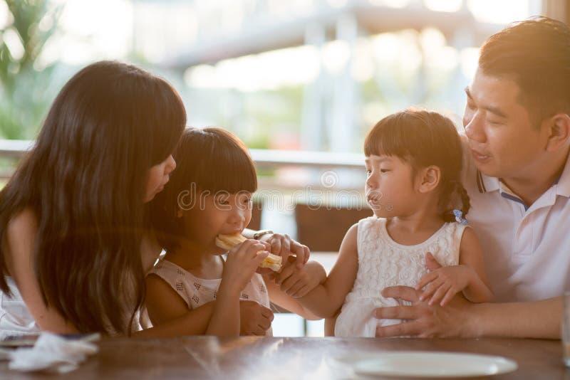 Asiatische Familie, die Lebensmittel am Café genießt lizenzfreie stockfotos