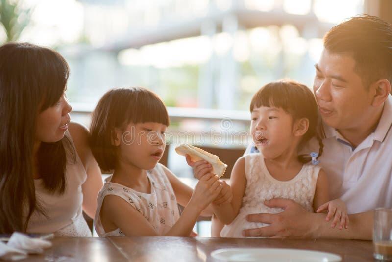 Asiatische Familie, die Mahlzeit am Café hat lizenzfreies stockfoto