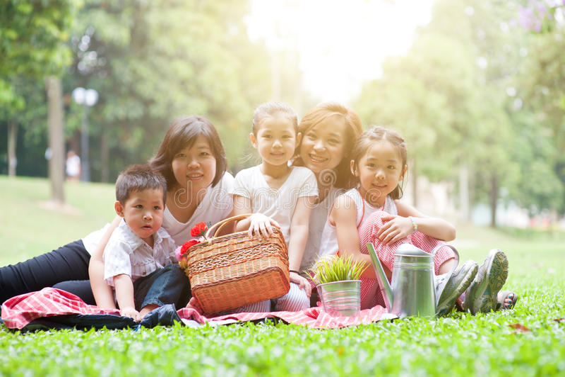 Asiatische Familie draußen picknicken lizenzfreie stockfotografie