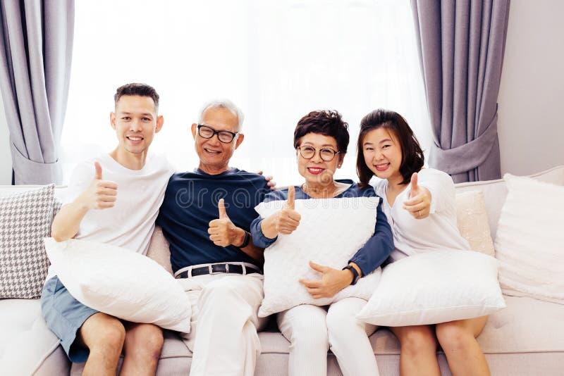 Asiatische Familie mit erwachsenen Kindern und älteren den Eltern, die Daumen aufgeben und sich zu Hause auf einem Sofa zusammen  stockfotografie