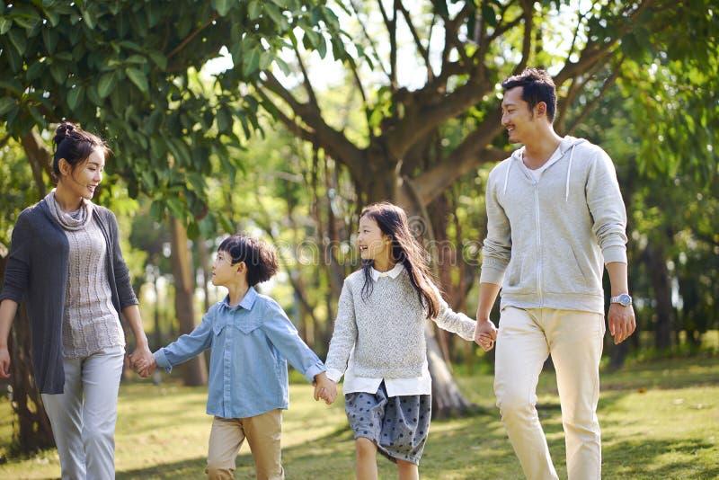 Asiatische Familie mit zwei Kindern, welche die Entspannung im Park gehen lizenzfreies stockfoto