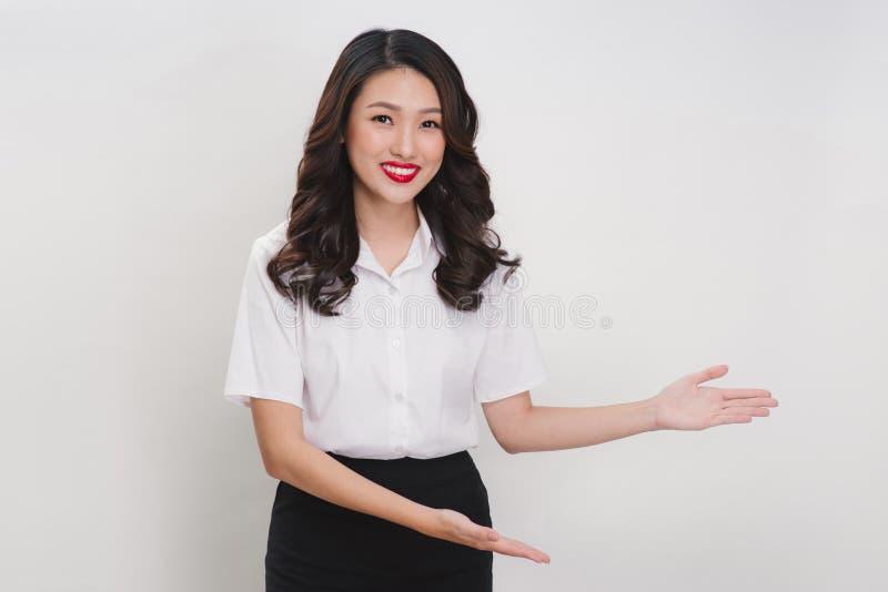 Asiatische Frau des Geschäfts, die willkommene Geste auf einem weißen Hintergrund tut lizenzfreies stockbild