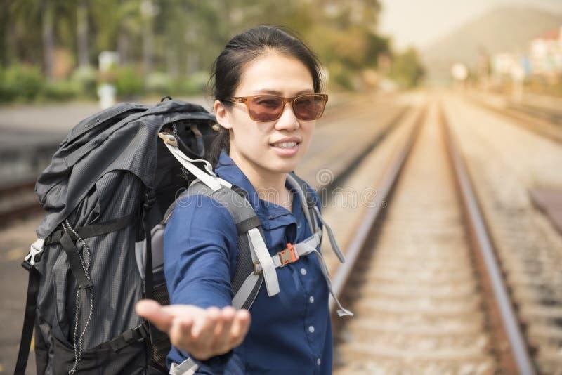 Asiatische Frau des glücklichen jungen Wanderers in der Showhand der legeren Kleidung außerhalb des Bahnhofs stockfotos