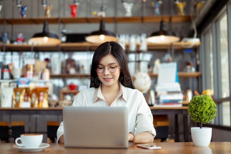 Asiatische Frau des gl?cklichen Freiberuflers, die unter Verwendung des digitalen Laptops arbeitet lizenzfreies stockbild