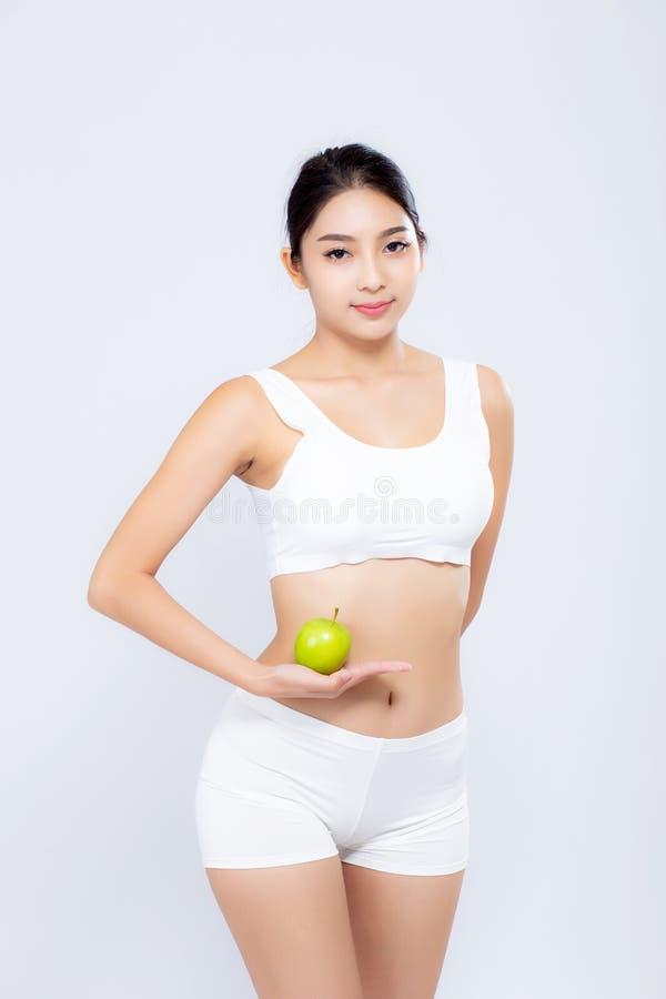 Asiatische Frau des Porträts, die grüne Apfelfrucht und schöne Körperdiät mit dem Sitz halten lokalisiert lächelt stockbild