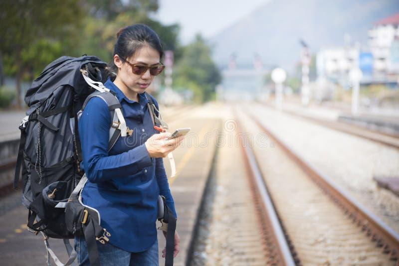 Asiatische Frau des Wanderers in der legeren Kleidung und in der Tasche an, Wartung den intelligenten Handy des Bahnzughandgriffs stockfoto
