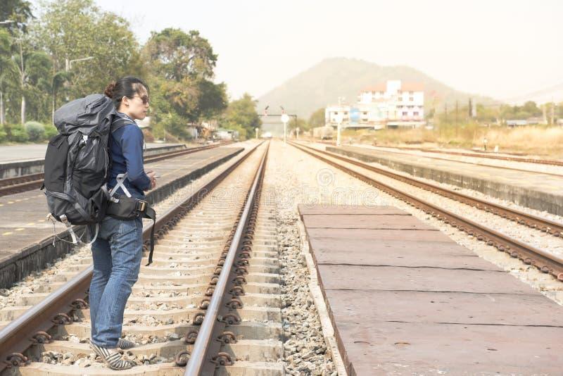 Asiatische Frau des Wanderers in der legeren Kleidung und in der Tasche an, Wartung den intelligenten Handy des Bahnzughandgriffs stockbild