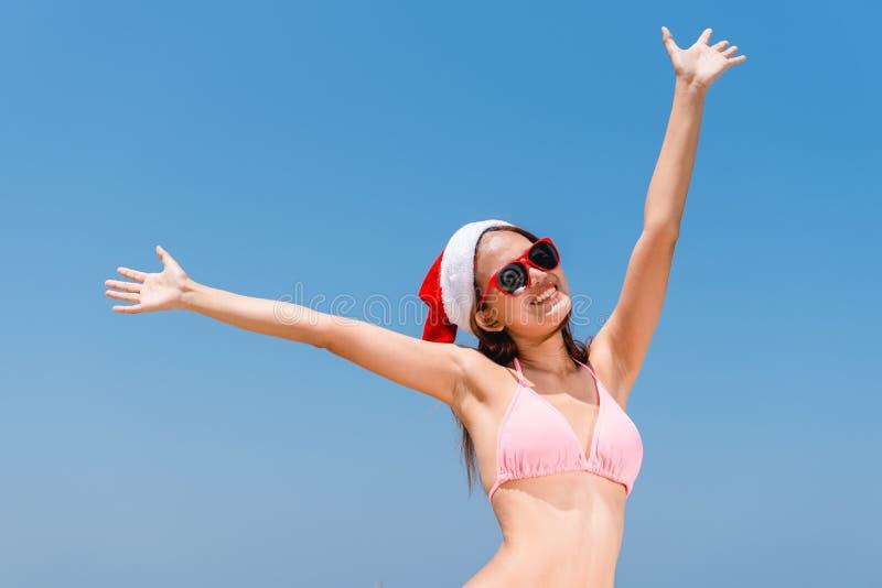 Asiatische Frau des Weihnachtsfeiertagsstrandspaßferien-Bikinis, die das sorglose Spritzwasser genießt Freiheit laufen lässt stockfoto
