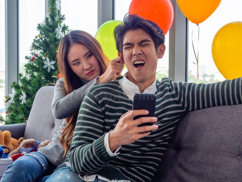 Asiatische Frau, die auf einem Sofa im Wohnzimmer saß, Ohren zog, weil ich wütend auf ihren Freund am Telefon war, der spielte stockbilder