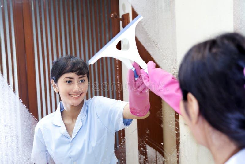Asiatische Frau, die Badezimmerspiegel aufräumt stockfoto