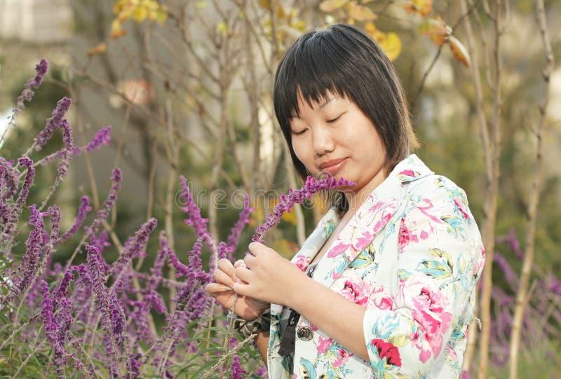 Asiatische Frau, die Blumen betrachtet lizenzfreie stockbilder