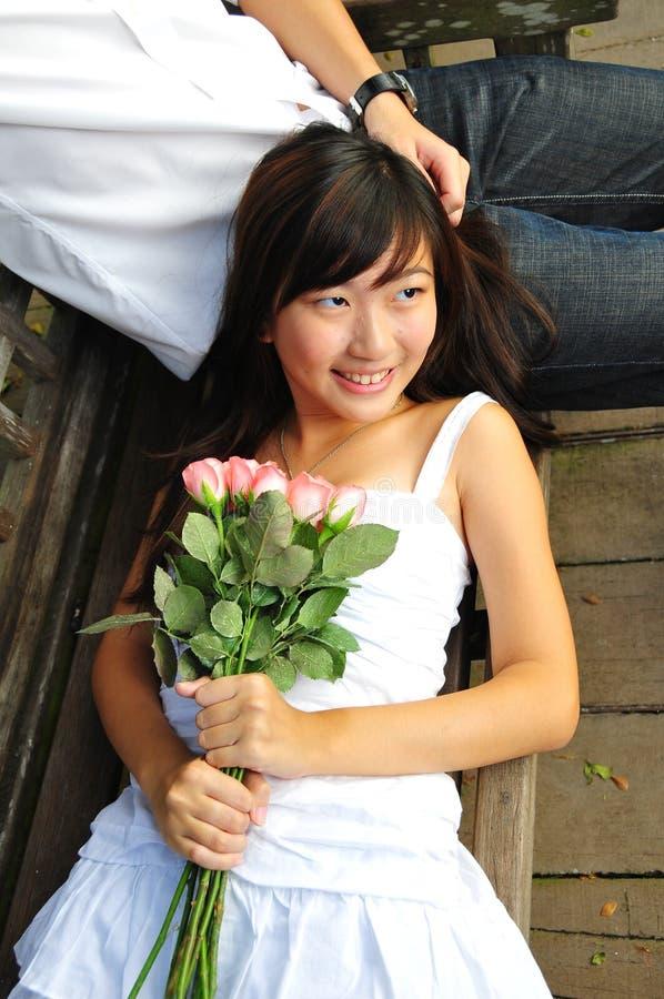 Asiatische Frau, die ein Bouguet der Blumen anhält lizenzfreie stockbilder