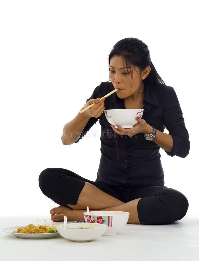 Asiatische Frau, die mit Hiebsteuerknüppeln isst stockbild