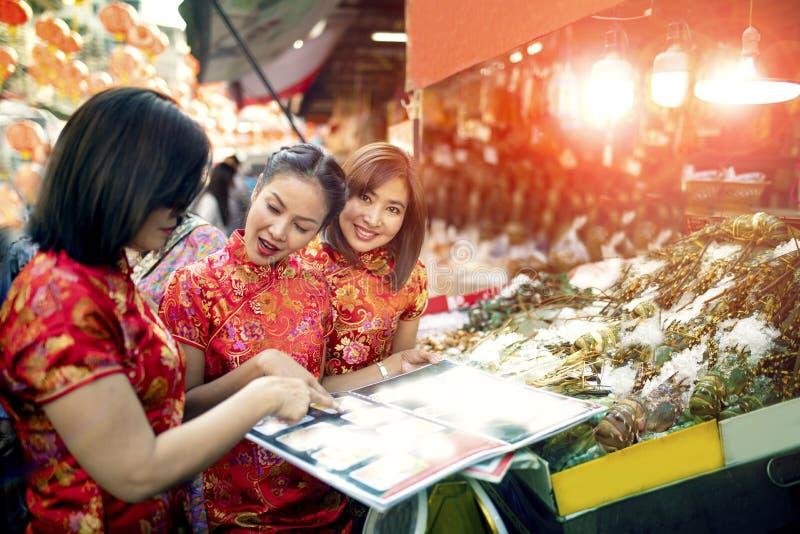 Asiatische Frau drei, die das chinesische Traditionskleidungsglück bereisend populärsten Reisen yaowarat Straße eine im und berüh stockfoto