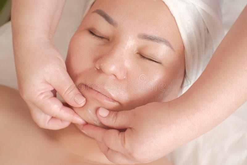 Asiatische Frau in einem Schönheitssalon Spezialistenwange mit Massage Gesichtssorgfaltverfahren lizenzfreie stockfotos