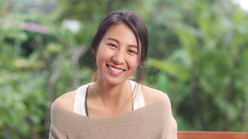 Asiatische Frau fühlt sich glücklich, wenn sie lächelt und fotografiert, während sie sich morgens auf dem Tisch im Garten zu Haus stockfotos