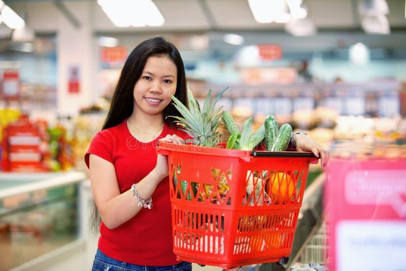 Asiatische Frau im Supermarkt lizenzfreie stockfotografie