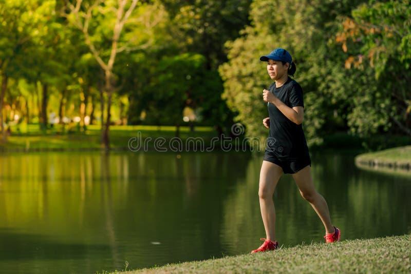Asiatische Frau von mittlerem Alter, die ein schwarzes Kleid, blauen Hut, laufendes in Park zum See nahe ausdehnen tr?gt Erhalten stockfotografie