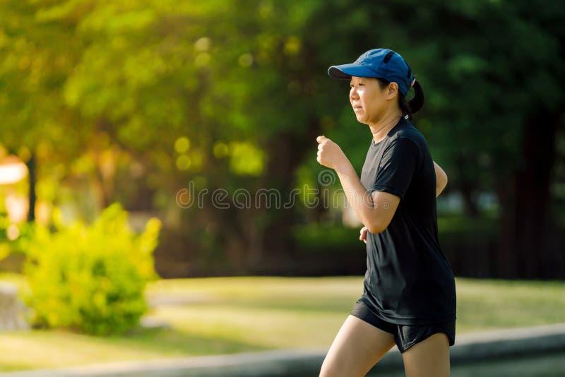Asiatische Frau von mittlerem Alter, die ein schwarzes Kleid, blauen Hut, laufendes in Park zum See nahe ausdehnen tr?gt Erhalten lizenzfreies stockbild