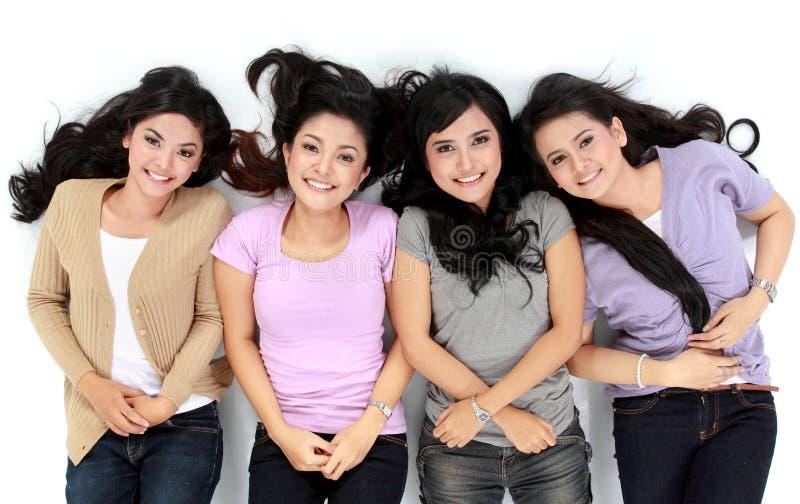 Asiatische Frauen, die das lächelnde Lügen auf dem Boden sich entspannen lizenzfreies stockfoto