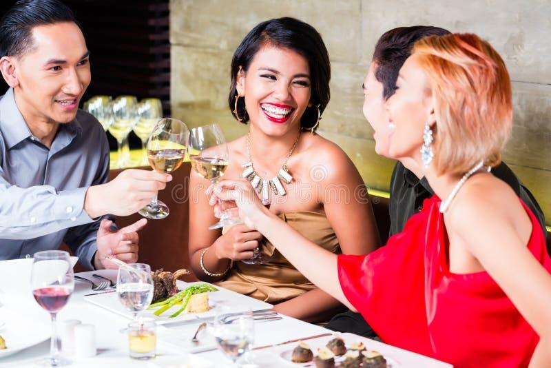 Asiatische Freunde, die im fantastischen Restaurant speisen stockfotos