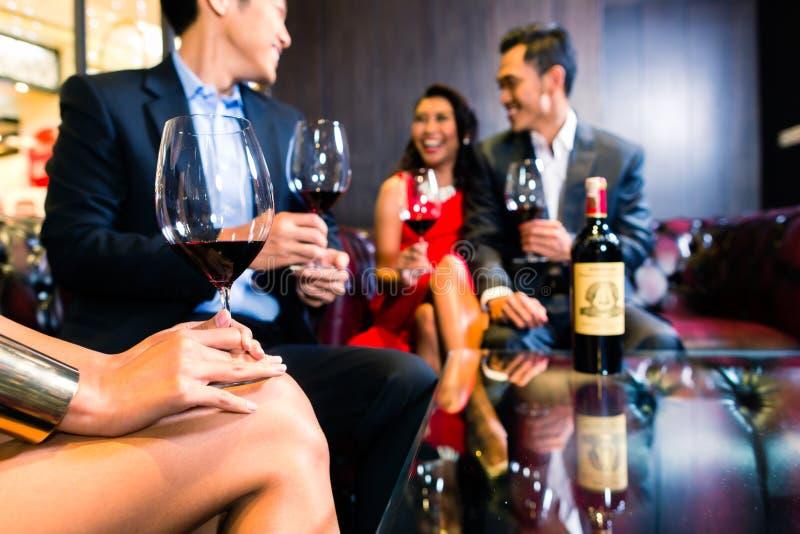 Asiatische Freunde, die Wein in der Bar trinken lizenzfreie stockbilder