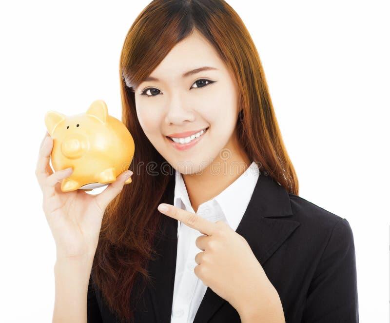 Asiatische Geschäftsfrau, die ein goldenes Sparschwein hält stockbild