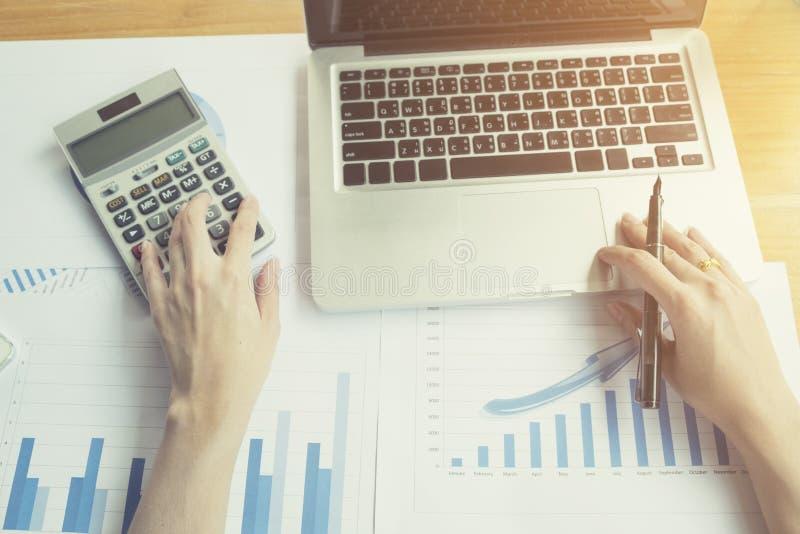Asiatische Geschäftsfrau, die einen Taschenrechner verwendet, um die Zahlen zu berechnen stockfoto
