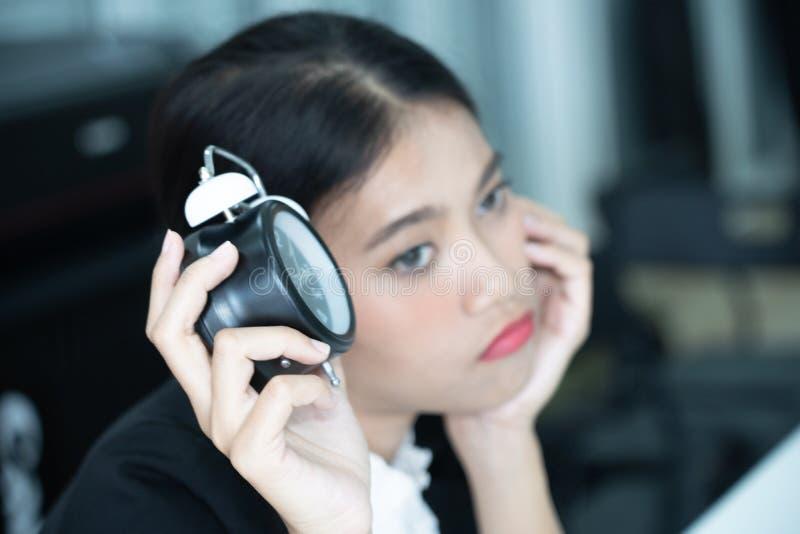 Asiatische Geschäftsfrau, die ermüdet und auf jemand wartend spät kommt bei der Arbeit gebohrt glaubt lizenzfreie stockfotos