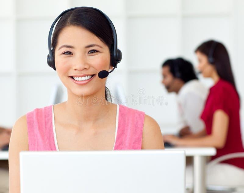 Asiatische Geschäftsfrau, die Kopfhörer verwendet stockbilder