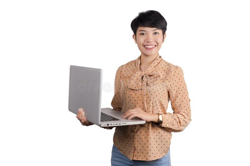Asiatische Geschäftsfrau, die Laptop auf grauem Hintergrund verwendet lizenzfreie stockbilder