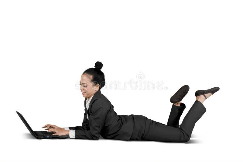 Asiatische Geschäftsfrau, die mit einem Laptop auf Studio liegt stockbild