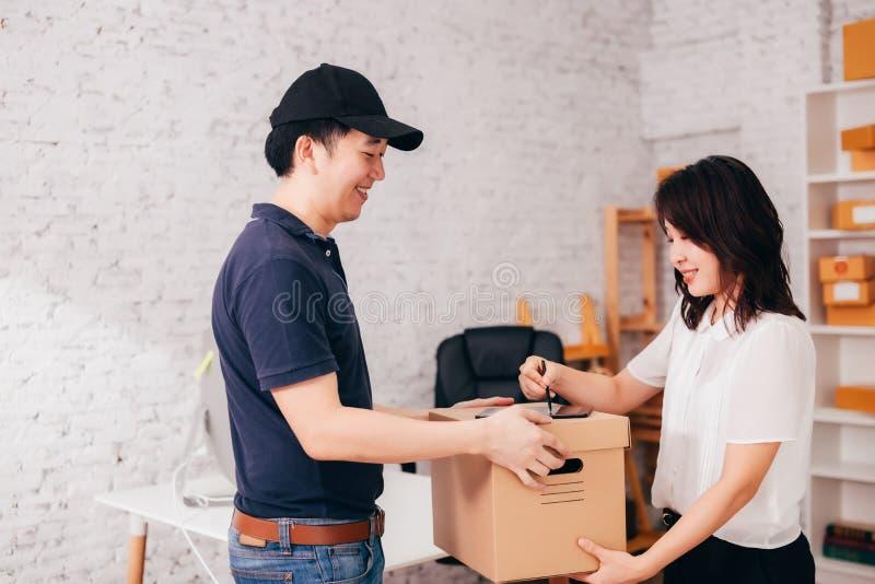 Asiatische Geschäftsfrau, die Paket vom Kurier empfängt lizenzfreies stockfoto
