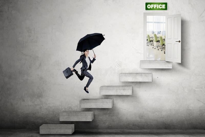 Asiatische Geschäftsfrau, die in Richtung zur Bürotür läuft lizenzfreies stockfoto
