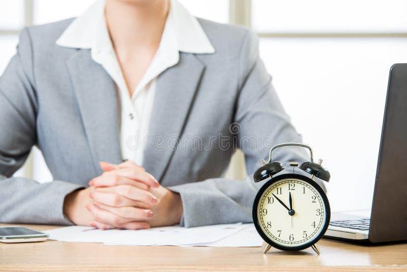 Asiatische Geschäftsfrau, die am Schreibtisch mit Wecker sitzt lizenzfreie stockfotos